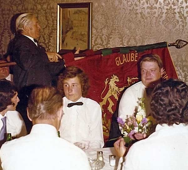 Fahnenübergabe der Schlösser-Amann-Fahne 1975. Helmut Amann mit der Fahne in der Hand. Der Knabe vor ihm mit der Fliege ist Thomas Gondorf